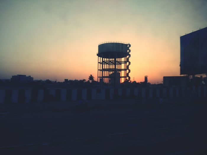 Water tower in factory against sky during sunset