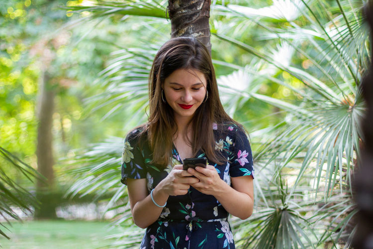 Young woman using phone while standing on palm tree