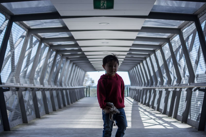 Boy standing in covered walkway