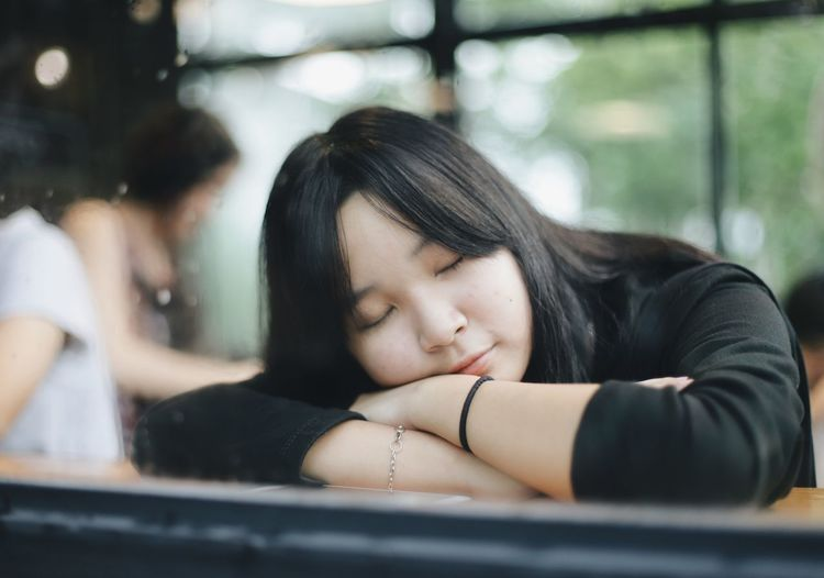 Headshot Women Portrait Eyes Closed  Black Hair Young Adult One Person Contemplation Hair Selective Focus Real People Window Emotion Adult Day Young Women Relaxation Indoors  Beautiful Woman Hairstyle Sleeping Sleep Nap Nap Time Sleepy Teenager Asian  Cafe Coffee Shop Girl
