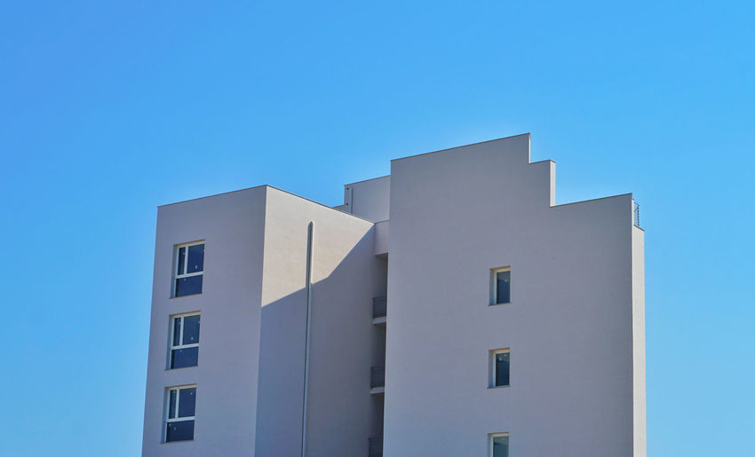 Low angle view of building against clear blue sky