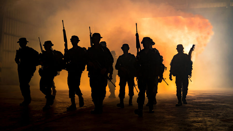 Silhouette people with weapons walking against smoke during sunset