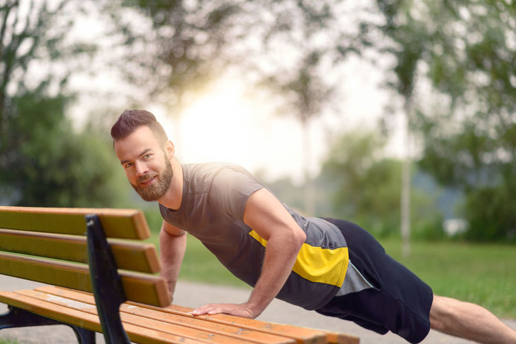 Portrait Of Smiling Man Doing Push-Ups On Bench In Park