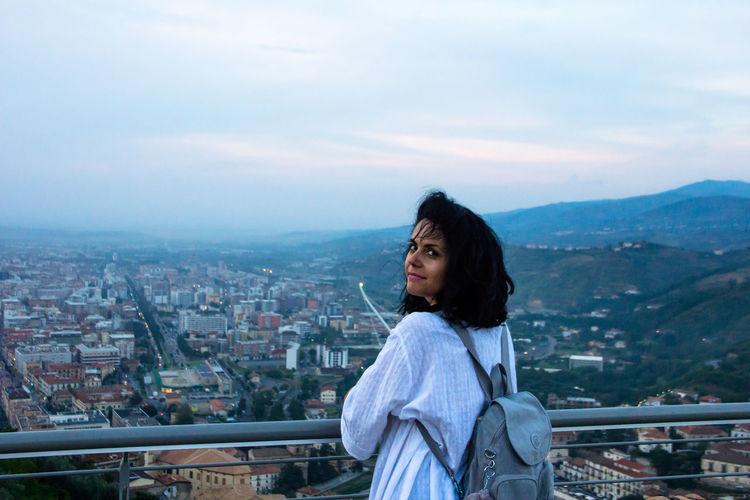 Portrait of young woman against cityscape