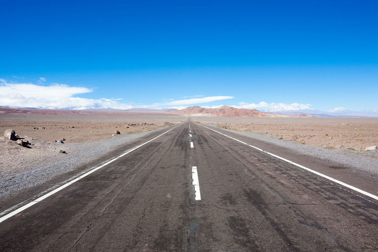View of road amidst desert against blue sky