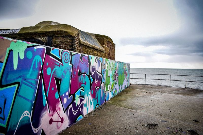 Urban lands end Graffiti Sea Sky Art And Craft Water Multi Colored Outdoors Street Art No People Day Architecture Cloud - Sky Built Structure Horizon Over Water Nature