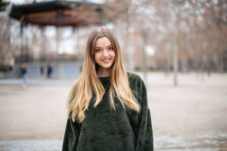 Portrait of smiling young woman with long hair standing in park during winter