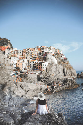 Rear view of woman sitting by sea on rock at cinque terre