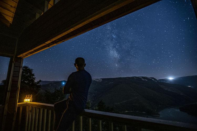 Rear view of man looking at sky at night