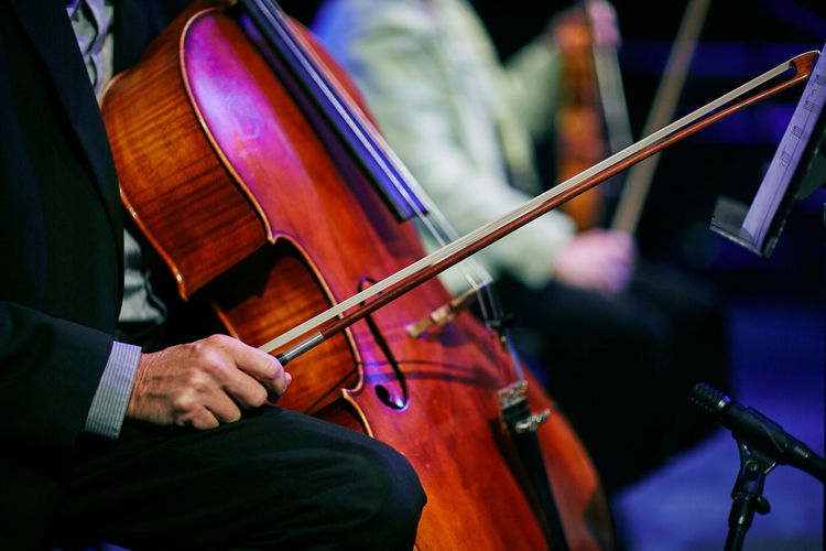 Midsection of musician playing cello on stage