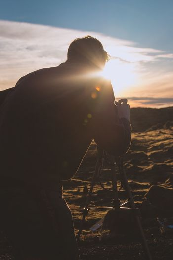 Photography Themes One Person Camera - Photographic Equipment Sunlight Real People Photographer Sky Outdoors Sunset Nature Lifestyles Day Leisure Activity Technology Men Digital Single-lens Reflex Camera Beauty In Nature Tripod SLR Camera Young Adult