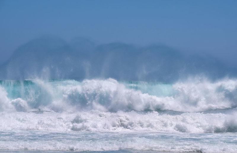 Waves splashing in sea against blue sky