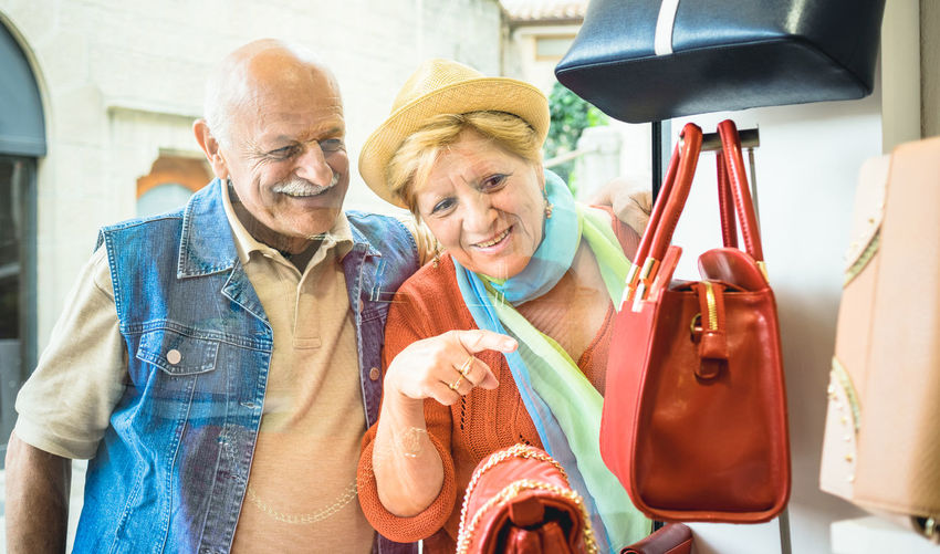 Senior woman pointing and showing man purse at retail display while standing outside store