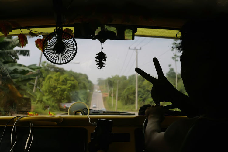 Silhouette man showing peace sign while driving car