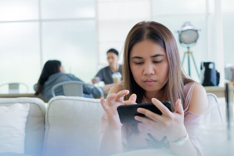 Woman using smart phone while sitting in cafe