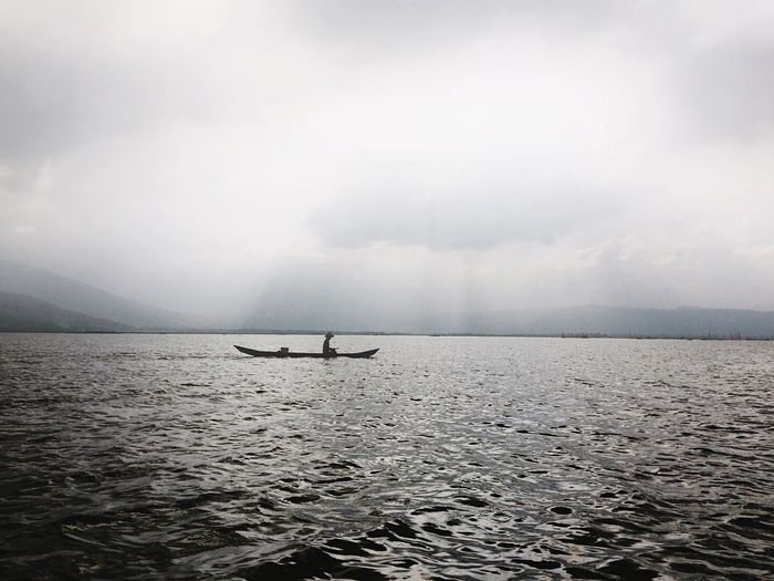 Man Rowing In Small Boat On Calm Lake