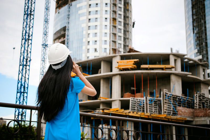 Female architect standing against incomplete building