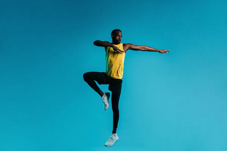 Man exercising against blue background