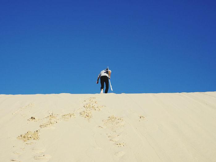 Full length of man on sand dune against clear sky