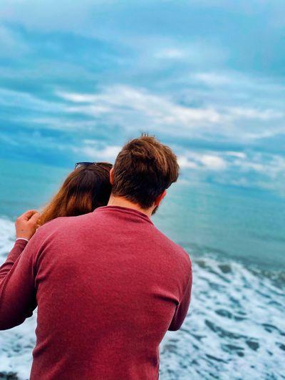 Rear view of man and woman looking at sea