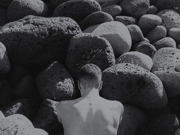 Shirtless Man In Front Of Rocks During Sunny Day