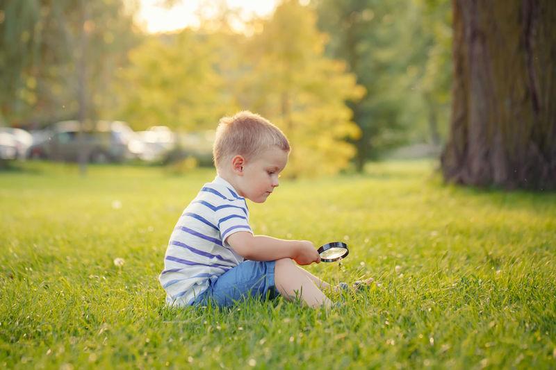 Boy sitting on field