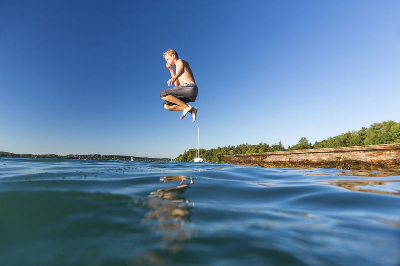 Shirtless man jumping on sea against clear blue sky