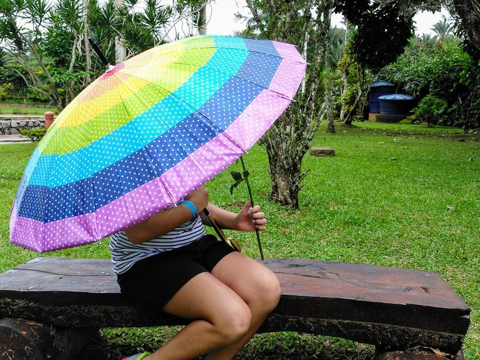 a girl sitting on a bench with a colorful umbrella Girl Bench Rainbow Lgbt Water Low Section Tree Summer Protection Fun Enjoyment Holding Women Grass Rainy Season RainDrop Below Sheltering Umbrella Monsoon Sunshade Parasol Underneath Beach Umbrella Canopy Sun Lounger
