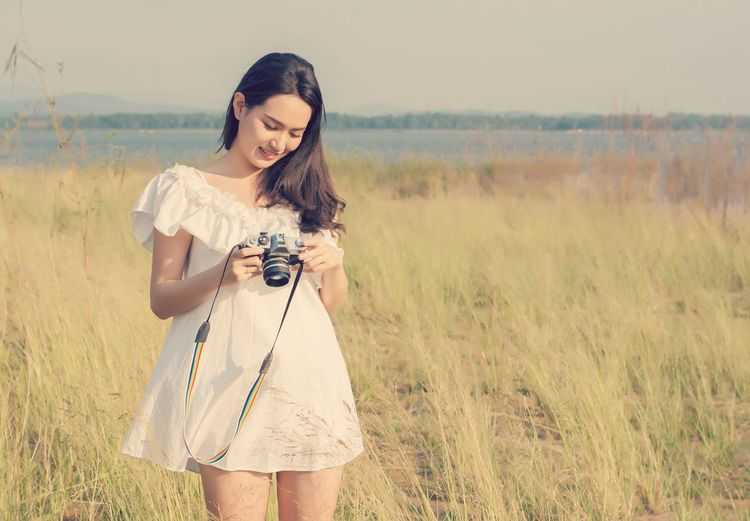 Young Woman Holding Camera While Standing On Grassy Field
