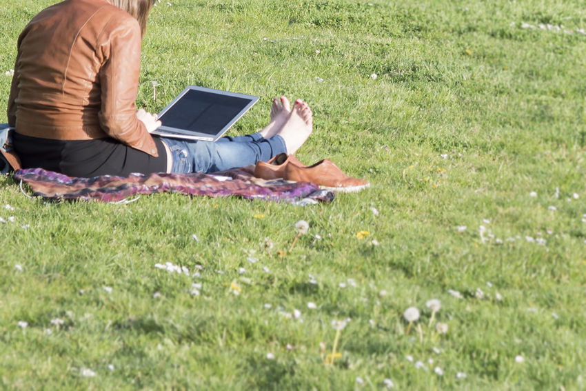 Barefoot using a laptop in the grass Adult Barefoot Computer Day Field Flower Grass Green Color Human Hand Low Section Millennials Mobile Nature One Person Outdoors People Real People Technology Telecommute Using Laptop Wireless Technology Women Working