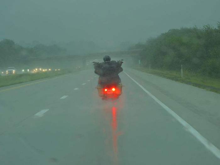 Motorcycle Photography Traveling In The Rain Braving The Elements Road Transportation Fog Direction Illuminated The Way Forward Sign One Person Symbol Rear View Mode Of Transportation Real People Street Tree Road Marking Diminishing Perspective Nature Marking Dusk Outdoors