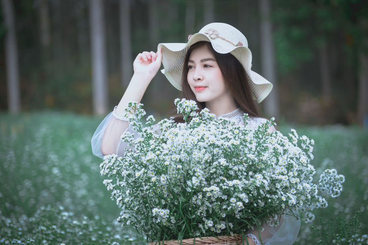 One Person Plant Clothing Hat Young Adult Flower Day Women Nature Front View Flowering Plant Focus On Foreground Portrait Young Women Waist Up Beauty Leisure Activity Adult Beautiful Woman Fashion Outdoors Sun Hat Hairstyle Contemplation