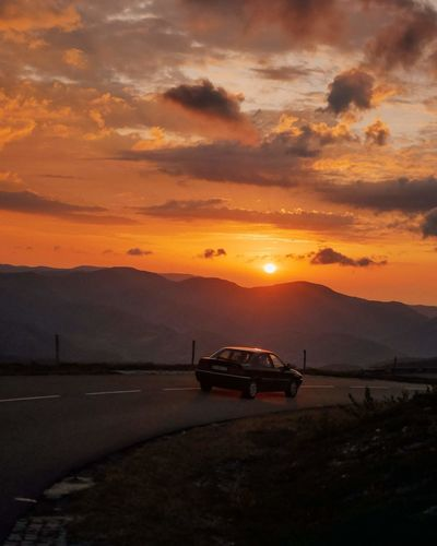 Car on road against mountain and sky during sunset