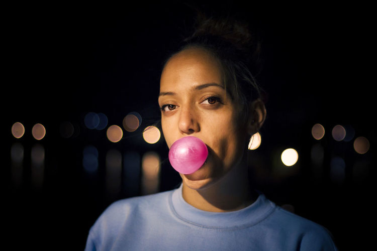 Close-up portrait of woman blowing bubble gum