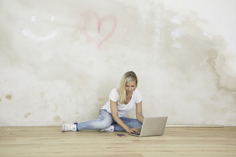 Young lady checking her computer on the floor in a yoga studio Casual Clothing Computer Graffiti Heart Leisure Activity Lifestyles Renovations Renovieren Wall