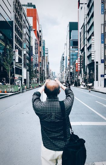 Rear view of man standing on city street