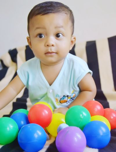 Cute boy sitting by balls on bed at home