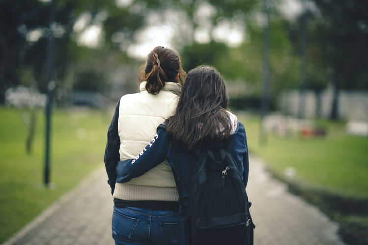 Rear view of mother and daughter embracing on footpath