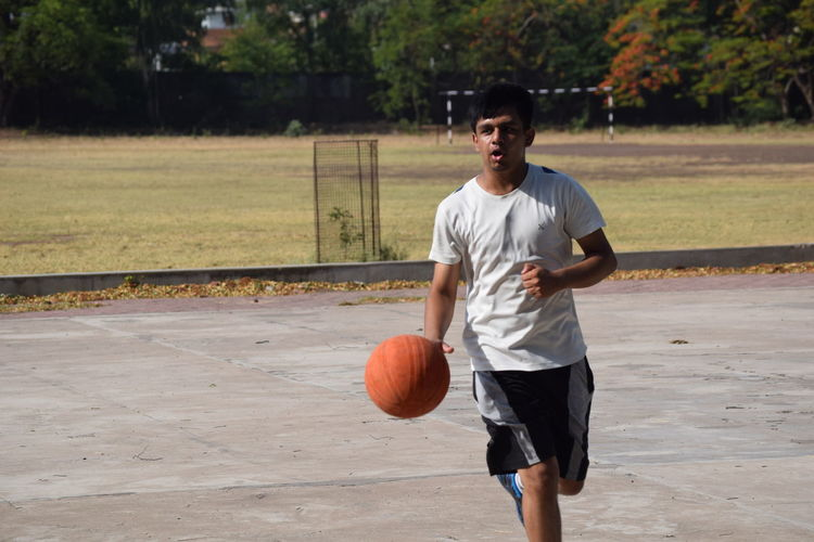 Young Man Playing Basketball On Court