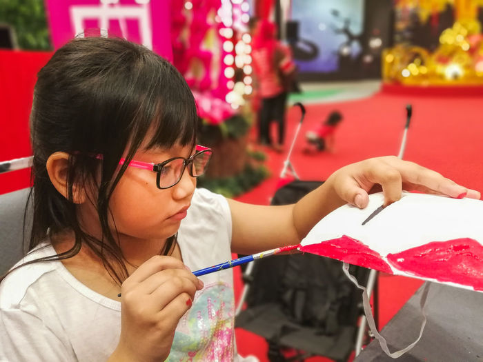 Close-up of cute girl painting craft product
