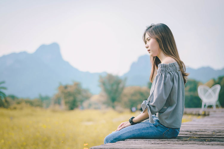 Young woman sitting on boardwalk against mountains