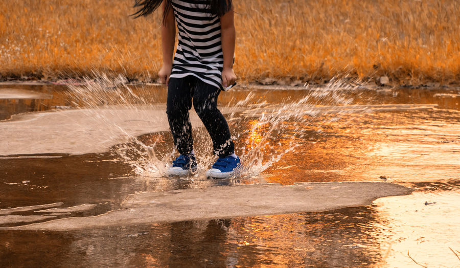 Splashing Water Splashing Water Splash Child Girl Playful Carefree Water Motion Low Section One Person Human Leg Real People Nature Lifestyles Body Part Wet Leisure Activity Sport Blurred Motion Day Men Standing Human Body Part Outdoors Spraying Flowing Water Human Limb