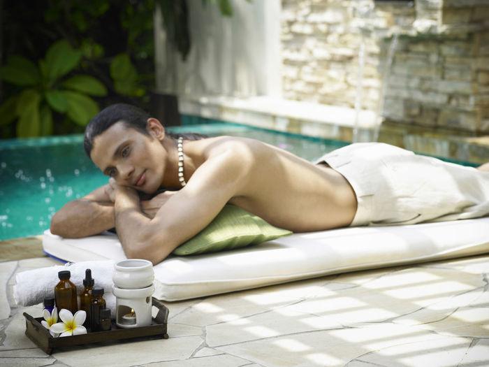 Shirtless man lying on poolside