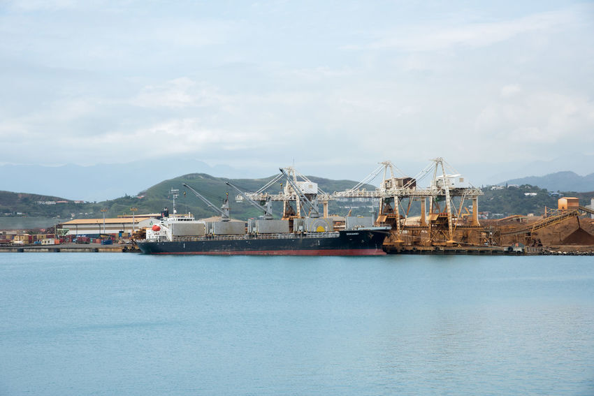 Noumea, New Caledonia-November 25,2016: Noumea shipyard with cranes, sea containers, ship and Pacific Ocean waters in New Caledonia. Gantry Cranes Noumea Architecture Cargo Container Commercial Dock Crane - Construction Machinery Day Freight Freight Transportation Harbor Industry Mode Of Transport Mountain Nautical Vessel New Caledonia Outdoors Sea Sea Container Ship Shipping  Shipyard Sky Transportation Water Waterfront