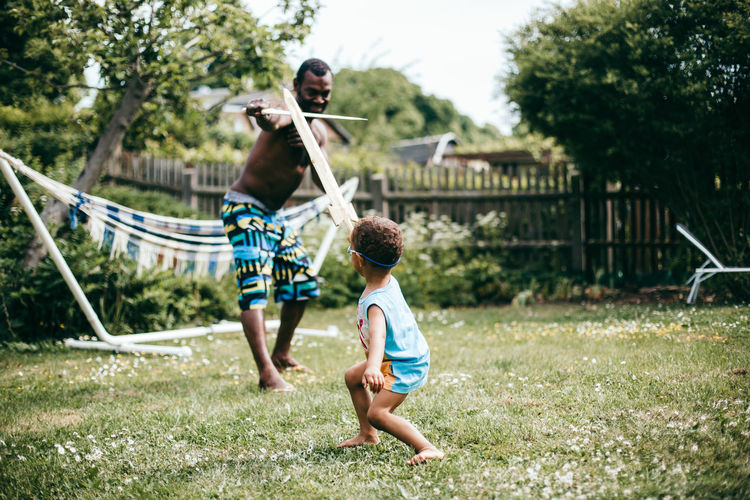 black father and son playing with wooden swords outdoors Emotions Family Family Matters Fatherhood Moments Fun Funny Joyful Man Summertime Black Emotion Family Time Father Father & Son Garden Joy Leisure Activity Leisure Games Outdoors Play Playful Son Summer Sword Sword Fight Moms & Dads