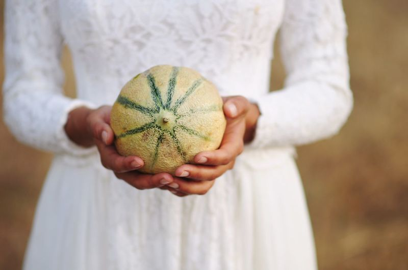 Midsection Of Bride Holding Melon Outdoors