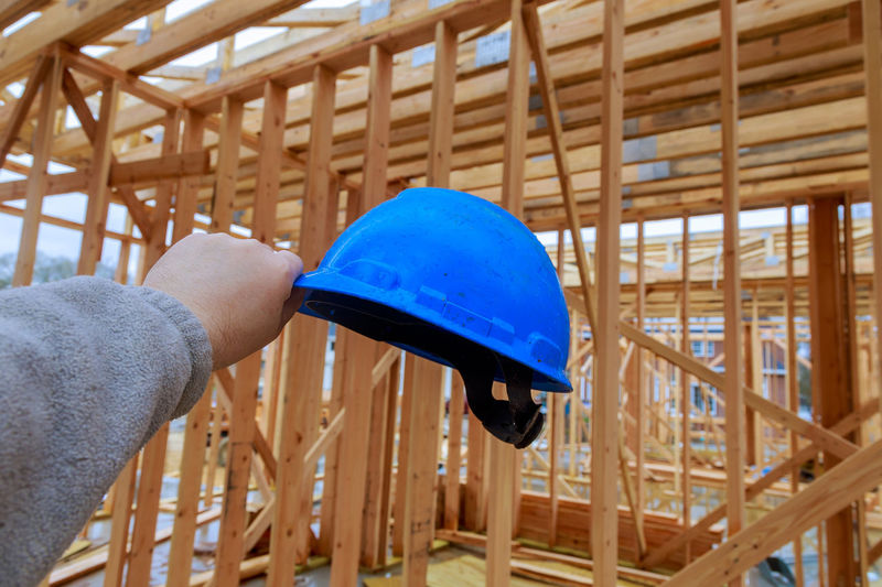 Midsection of man holding umbrella at construction site