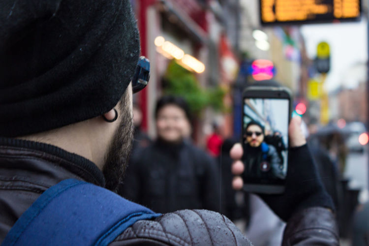 Rear view of man taking selfie with mobile phone in city