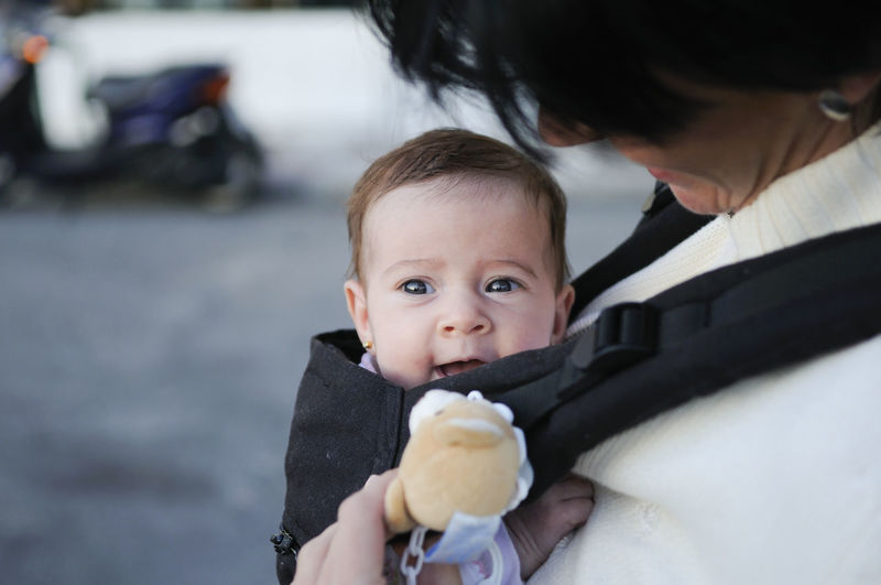 Mother carrying her baby girl in a baby carrier outdoors Two People Headshot Portrait Child Holding Childhood Baby Young Focus On Foreground Mid Adult Eating Day Togetherness Food Females Babyhood Males  Front View Innocence Care Outdoors