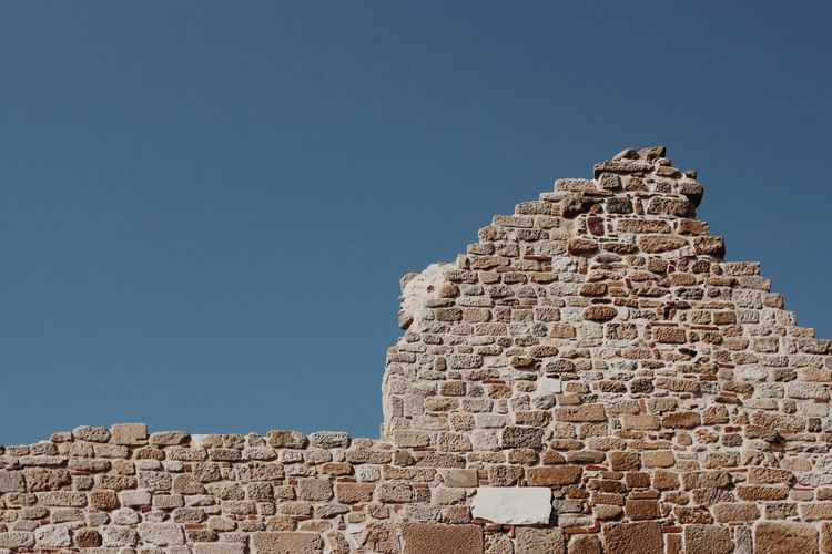 Low angle view of stone building against clear blue sky